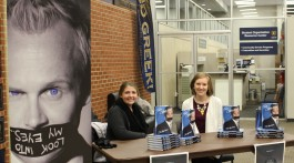 """Cru students help to sell Jim Monroe's book, """"The Charlatan: The Skeptical, Mysterious, Supernatural True Story of a Christian Magician,"""" after the show. (Photography by Zoe Hester, East Tennessean)"""
